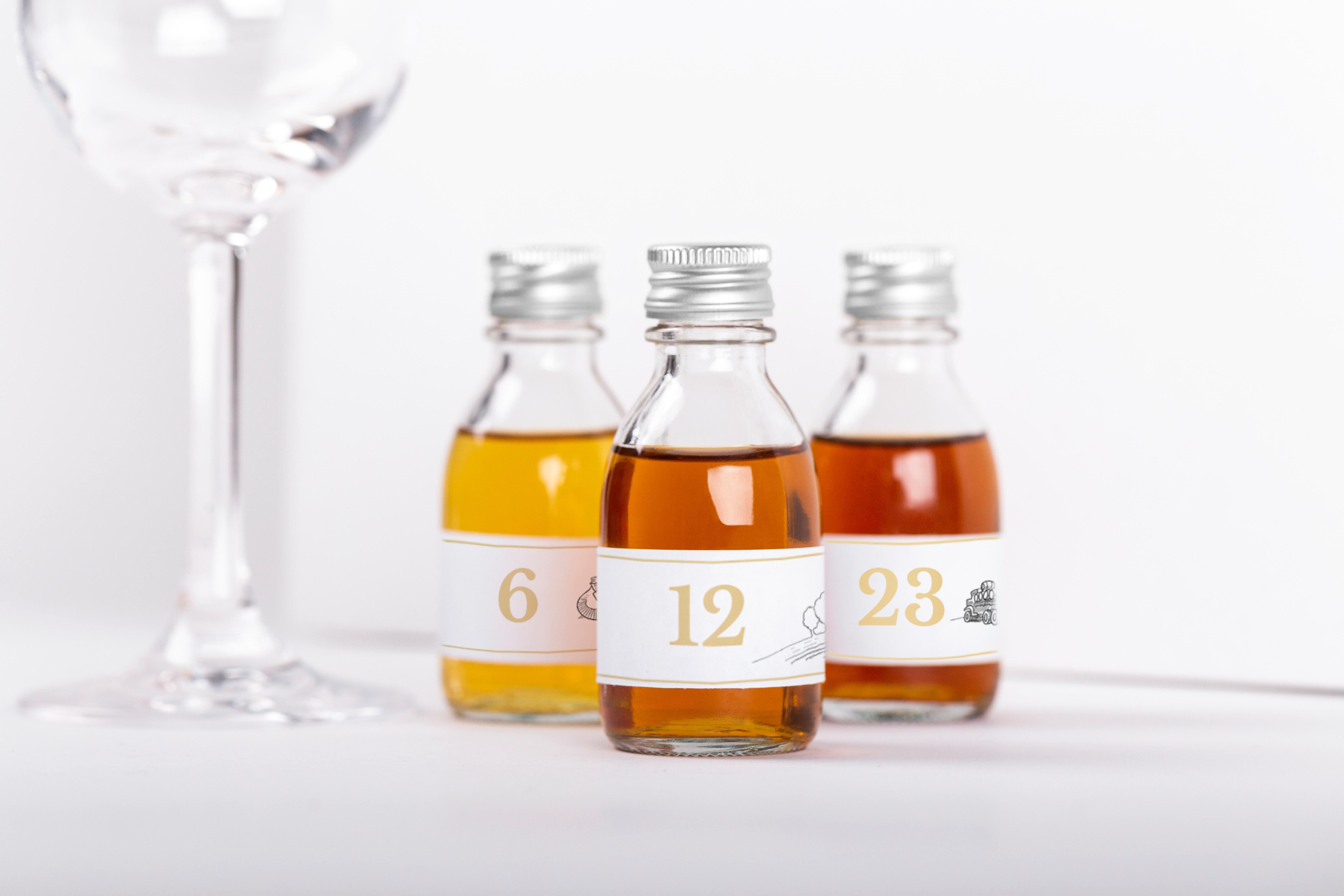 3 cognac sample bottles next to tasting glass