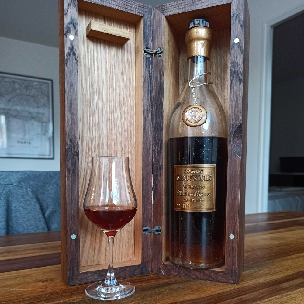 Mauxion Sélection Multimillésimes Cognac in wooden box next to glass filled with cognac